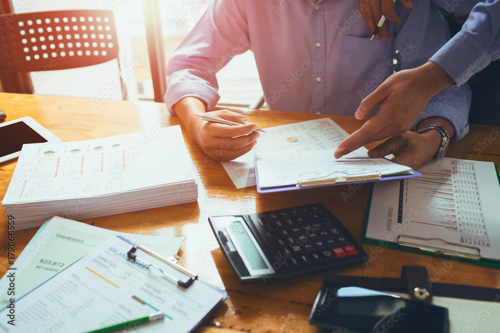 Fototapeta Business man accountant working hard with accounting financial report of annual 2017 with tax paperwork or job order product.