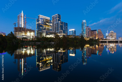 Photo Stands Austin, Texas with new buildings rising, reflecting in lady Bird Lake during sunset / Austin Skyline and new constructions