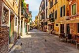 Fototapeta Uliczki - Narrow street in the old town in Venice Italy