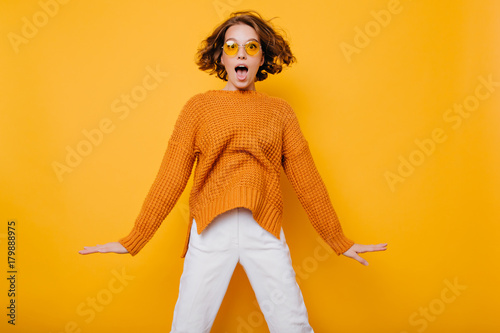 5f447b4ac Portrait of surprised young woman in white pants jumping in front of ...