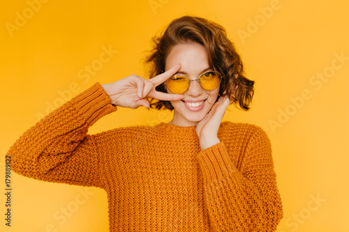 Joyful european girl with shiny curls laughing and showing peace sign on yellow background. Indoor portrait of beautiful lady in glasses and knitted clothes having fun in studio.