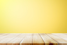 Empty Wooden Deck Table Over Yellow Wallpaper Background.