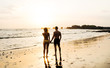 Happy couple in love is watching the sunset on a wild sand beach. Silhouettes of sporty man and woman in swimming suits holding hands while standing on a sea cost at nightfall during summer vacation.