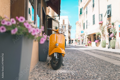Vintage orange scooter standing in street of Alghero. Sardinia. Italy.