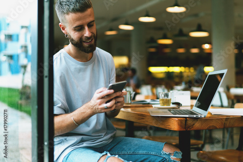 Smiling bearded young man is texting messages on a mobile phone while chatting with a  friend. Cheerful hipster guy is searching information about interesting city events on smartphone.