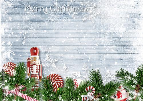 Fotografía  Christmas border with fir branches, nutcracker, candy and snowfall