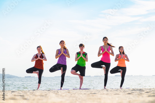 Deurstickers Ontspanning yoga group of people doing tree pose and namaste with calm relax emotion at beach,Meditation pose,Wellness and Healthy Lifestyle.