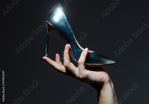 Shoe on high heel, stiletto, in hand on grey background Poster Mural XXL