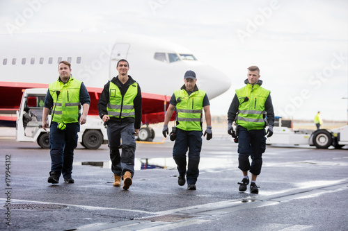 Foto  Confident Workers Walking On Runway During Rainy Season