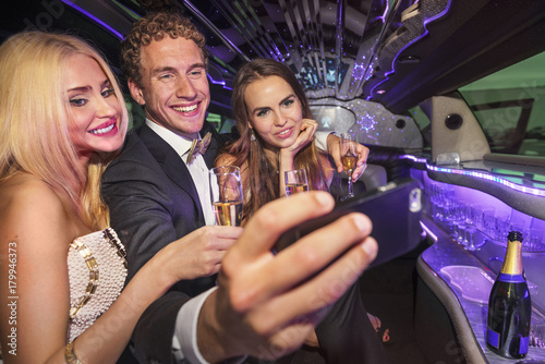 Successful young male in a limousine with two beautiful woman