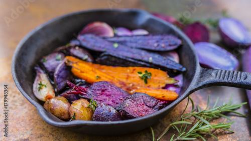 Fototapeta Pieczone warzywa z ziołami na patelni żeliwnej.