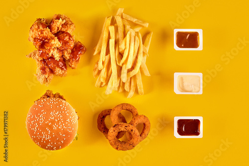 Meat Burger Potato Chips And Wedges Take Away Composition French Fries Hamburger Mayonnaise Ketchup Sauces On Yellow Background