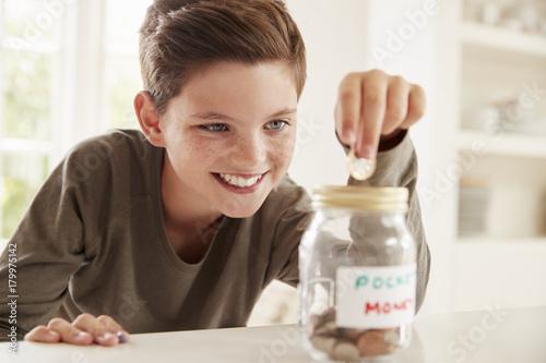 Photo Boy Saving Pocket Money In Glass Jar At Home