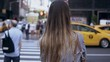 Back view of young beautiful woman crossing the road in New York, America. Female looking on the riding cars and taxi.