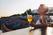 Italy, Santa Caterina, woman relaxing on promenade with glass of Spritz at sunset