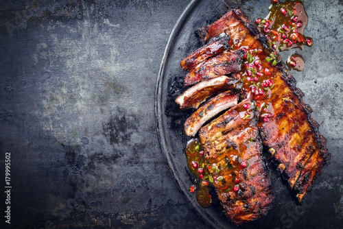 Barbecue pork spare ribs with fruit relish as top view on an old rustic board with copy space