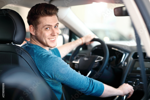 Fotomural Happy young male driver behind the wheel