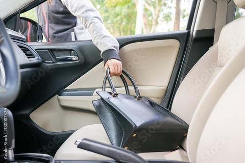 Woman burglar steal a shoulder bag through the window of car - theft concept Tapéta, Fotótapéta