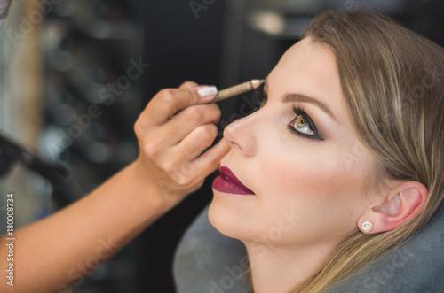 Ótimo conceito de maquiagem, maquiadora maquiando jovem mulher loira Wallpaper Mural