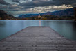 Bled, Slovenia - Sunset at the beautiful Lake Bled with Pilgrimage Church of the Assumption of Maria and pier and amazing clouds at autumn