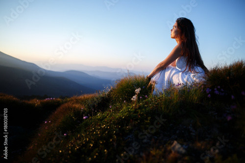 Poster Marron chocolat Beautiful woman in a long white dress in the mountains. Young woman sitting on a rock. Hair blowing in the wind. Girl relaxing outdoors. Beautiful woman posing in tall grass