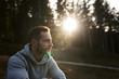 canvas print picture - Mann sitzt im Wald und die Sonne geht unter