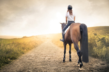 Girl riding her horse in a path in the hills
