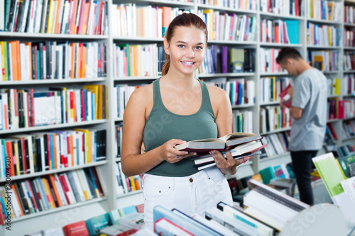 Foto  Interested teenager girl customer reading book