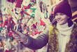 Young girl buying Christmas decoration at market