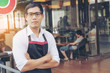 Asia man owner or waiter wear apron in coffee shop with copy space. Sunlight by Soft flare filter.