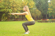 Young woman doing exercises in park