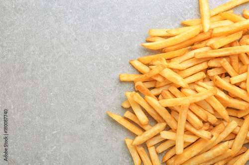 Yummy french fries on grey background