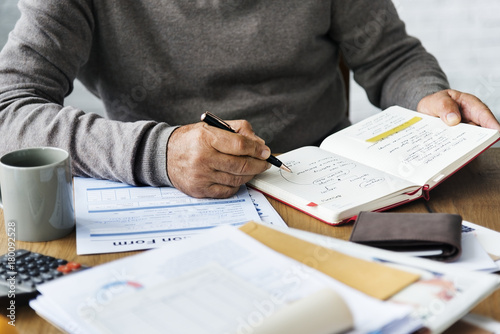 Senior man writing down some notes Canvas