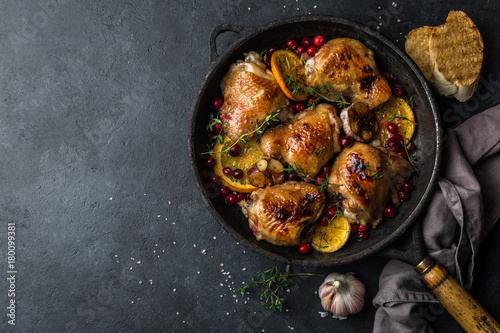 Photo  roasted  chicken with orange, cranberry and spicy herbs on pan