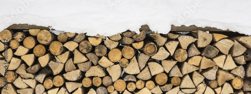 Foto op Plexiglas Brandhout textuur Firewood Logs Covered with Snow. Winter Texture Pattern Background.
