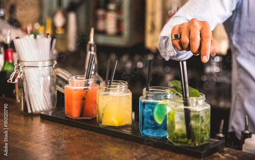 Bartender hand at multicolored fashion drink with straw on vintage glass cups in Canvas-taulu
