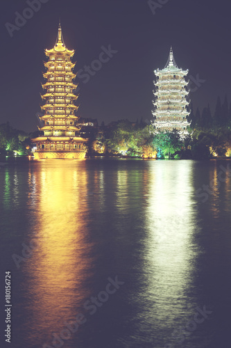 Tuinposter Guilin Guilin Sun and Moon Tower Pagodas in Fir Lake at night, color toned picture, China