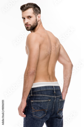 Poster Akt Sexy back. Rear view of young shirtless man in jeans looking at camera while standing against white background.