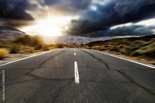Straße führt ins Gebirge während Sonnenuntergang Plakat