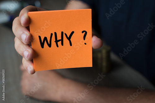 Fotografía  Hand holding an orange Paper with the word why - Why?, Business Concept