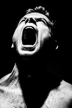 Angry Man Screams On A Black Background, Aggression