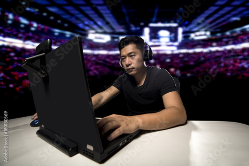 фотографія  Competitive asian male professional E Sports video gamer playing an FPS, or MMO game on a computer and streaming online