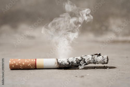 Photo  Close up cigarette burning on concrete floor , stop quitting tobacco concept