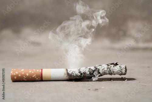 Fotografija  Close up cigarette burning on concrete floor , stop quitting tobacco concept