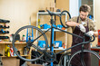 Man in apron and gloves fixing handlebars of bicycle in workshop