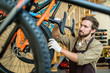 Young man checking tires and seats of new bicycles in bikeshop