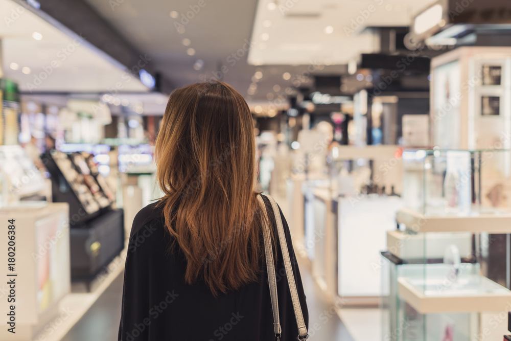 Fototapeta Young asian woman walking in cosmetics department at the mall