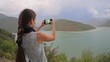 A young lady taking photos near the lake in the mountains. Medium shot.
