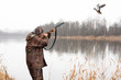canvas print picture - hunter shooting to the flying duck
