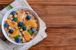 Light porridge with toppings. Oatmeal with juicy mandarins, blueberries, hazelnuts and mint in a white bowl and on a wooden background with copy space. Low calorie porridge recipe. Top view
